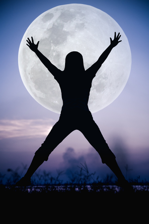 cool colors: Silhouette back view of woman enjoying and jumping at riverside. Large full moon with fantastic sky background. Happy time on vacation. Cool colors tone effect. The moon were NOT furnished by NASA.