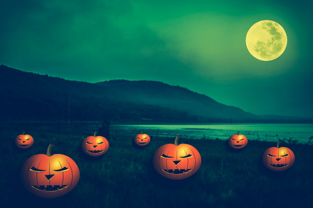 not full: Mountain and beautiful full moon, outdoors at night.  Pumpkins with scary face on the riverbank. Vintage green background for Halloween holiday. The moon were NOT furnished by NASA. Stock Photo