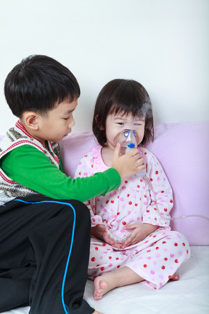 nursing sister: Asian child was bronchitis and crying. Kindly brother take care his sister with asthma problems making inhalation by mask at hospital. Happy family concept, loving and bonding of sibling. Stock Photo