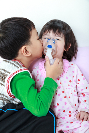 nursing sister: Asian child was bronchitis and crying. Loving brother take care his sister with asthma problems making inhalation by mask at hospital. Brother kiss on cheek his sister, loving and bonding of sibling. Stock Photo