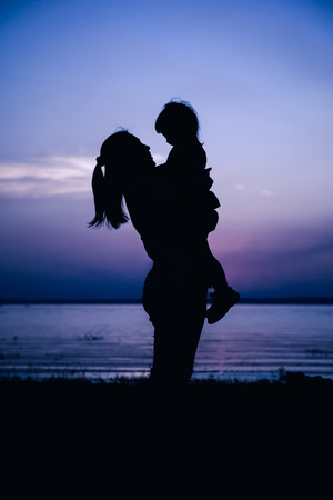cool colors: Silhouette side view of mother and child enjoying at riverside. Mother carrying her daughter. Happy family spending time together. Friendly family. Cool colors tone photo effect.