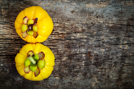 citric: Top view. Two garcinia cambogia fruit on wood background and free form copy space. Garcinia atroviridis is a spice plants and hydroxy citric acids (HCA) for good health. Stock Photo