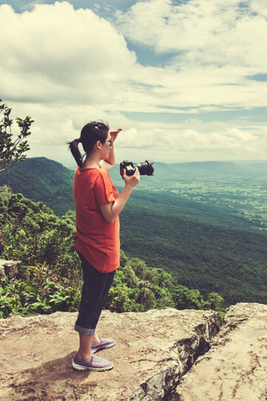 tropical evergreen forest: Asian woman photographed the beautiful view by digital camera at view point on mountain. Pretty sky with cloudy, outdoor at the daytime on summer day, tropical evergreen forest. Cream tone.