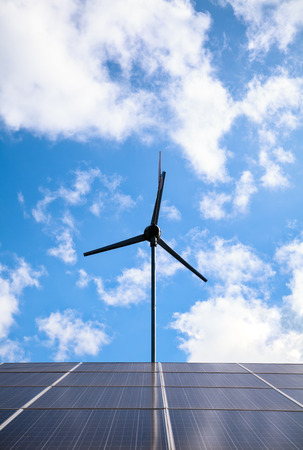 Solar panels and wind turbine for electric power production, alternative energy resources. Solar Panels and wind turbines generating green energy against blue sky with clouds background. Outdoors.