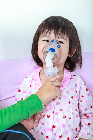nursing sister: Sad asian child was bronchitis and crying. Kindly brother take care his sister with asthma problems making inhalation by mask at hospital. Happy family concept, loving and bonding of sibling. Stock Photo