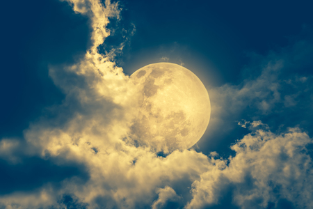 Attractive photo of a nighttime sky with cloudy and bright moon. Beautiful nature use as background. Outdoors at night. Vintage tone effect. The moon were NOT furnished by NASA.