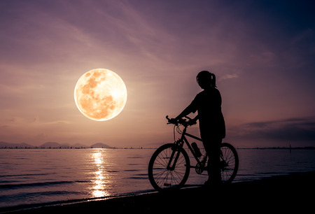 Silhouette of healthy biker-girl enjoying the view at seaside, beautiful full moon on colorful sky background. Reflection of moon in water. Outdoors. The moon were NOT furnished by NASA. Stock Photo