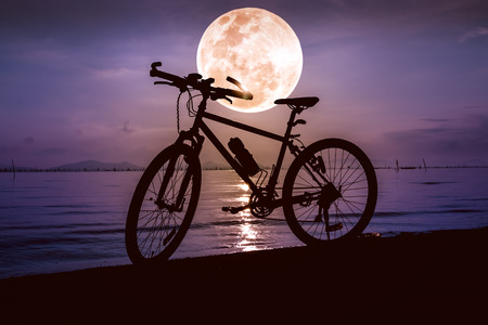 Silhouette of bicycle on the beach against beautiful full moon on colorful sky background. Outdoors. The moon were NOT furnished by NASA.