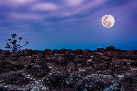 Rocky against colorful sky and beautiful full moon at night. Beauty of nature use as background. Outdoors. The moon were NOT furnished by NASA.
