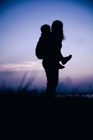cool colors: Silhouette side view of mother and child enjoying at riverside. Mother giving children piggyback. Happy family spending time together. Friendly family. Cool colors tone photo effect. Stock Photo