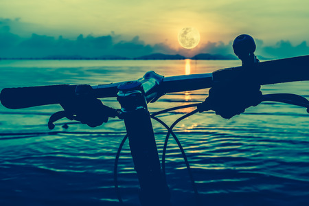 full moon effect: Silhouette of a parts bicycle, handlebar on the beach against bright full moon in the sea. Reflection of moon in water. Outdoors. Cross process and vintage tone effect.