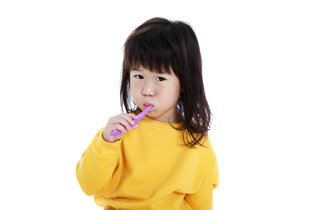 oral health: Closeup cute asian girl in pajamas with a toothbrush in hand and brush teeth, oral health concept. Isolated on white background. Sleepy chinese child waking up early in the morning. Stock Photo