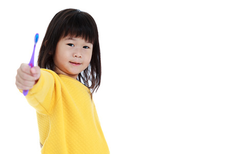 oral health: Sleepy asian child in pajamas with a toothbrush, oral health concept. Isolated on white background. Cute chinese girl waking up early in the morning and show her toothbrush. Stock Photo