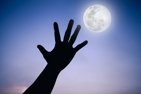 full moon effect: Silhouette of a hand with full moon on fantastic sky background. Symbol is mean to say hi , five , hand up, stop. Outdoors. Outdoor. Cool colors tone photo effect.