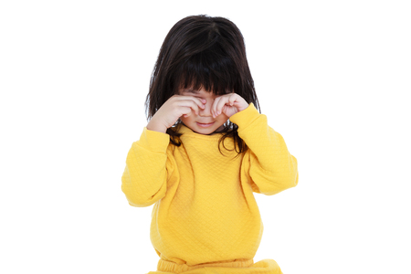 Chinese child waking up, girl looks sleepy in the morning, isolated on white background. A tired asian girl in pajamas rubbing eyes.