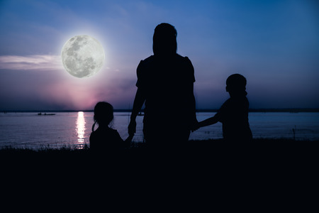 full moon effect: Silhouette of parent and child enjoying the view at riverside. Colorful blue sky and bright full moon background. Friendly family. Cool colors tone photo effect. The moon were NOT furnished by NASA.
