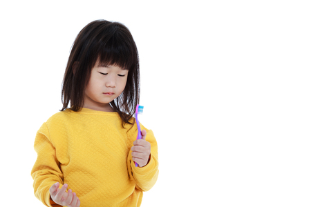 oral health: Sleepy asian child in pajamas with a toothbrush, oral health concept. Isolated on white background. Cute chinese girl waking up early in the morning and looking at her toothbrush. Stock Photo