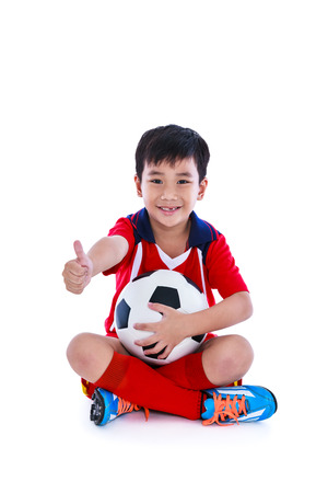 Full body of young asian soccer player in sportswear tooth smile and holding his soccer ball. Handsome boy with thump up sitting on the floor at studio. Isolated on white background. Positive emotion.