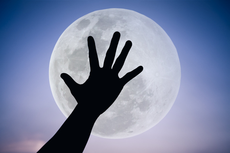 full moon effect: Silhouette of a hand with large full moon on fantastic sky background. Symbol is mean to say hi , five , hand up, stop. Outdoors. Outdoor. Cool colors tone photo effect.