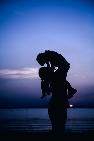 cool colors: Silhouette of mother and child enjoying the view at riverside. Mother lifting her little girl up in the air on colorful sunset sky background. Friendly family. Cool colors tone photo effect.