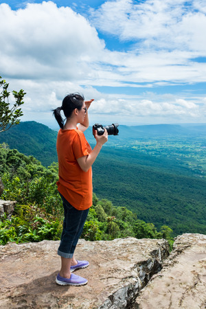 tropical evergreen forest: Asian woman photographed the beautiful view by digital camera at view point on mountain. Pretty sky with cloudy, outdoor at the daytime on summer day, tropical evergreen forest.