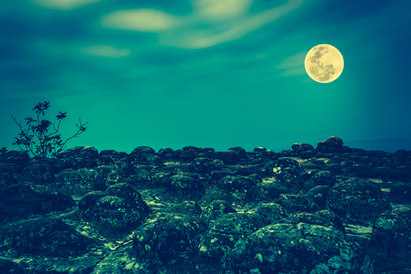 Rocky against colorful sky and beautiful full moon at night. Beauty of nature use as background. Outdoors. Cross process and vintage tone effect. The moon were NOT furnished by NASA.