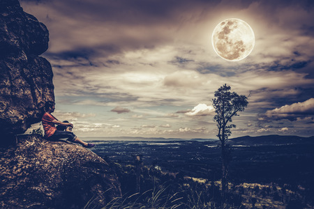 Woman sitting on boulders and looking at  sky with cloudy and beautiful full moon over tranquil nature nighttime. Low key and high contrast style. The moon were NOT furnished by NASA. Stock Photo