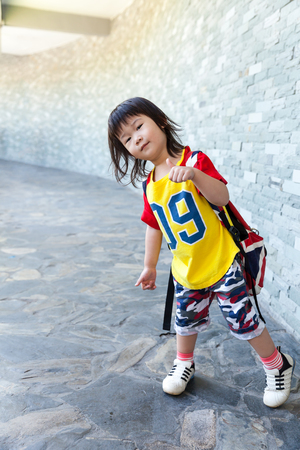 thump: Full body of happy asian girl with thump up and looking at camera on blurred gray  wall background. Tourist child relaxing outdoors at the daytime, travel on vacation. Positive human emotion. Stock Photo