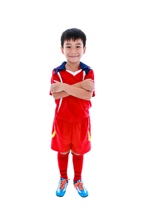 Full length portrait of young asian soccer player in red uniform smiling and looking at camera, studio shot. Isolated on white background. Stock Photo