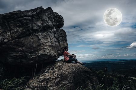 not full: Woman sitting on boulders and looking at  sky with cloudy and beautiful full moon over tranquil nature nighttime. Low key and high contrast style. The moon were NOT furnished by NASA. Stock Photo