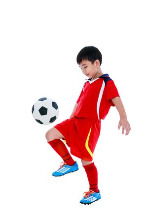 Het volledige lengteportret van gelukkige Aziatische voetballer in rode eenvormig stuitert zijn voetbalbal, studioschot. Geïsoleerd op witte achtergrond Stockfoto