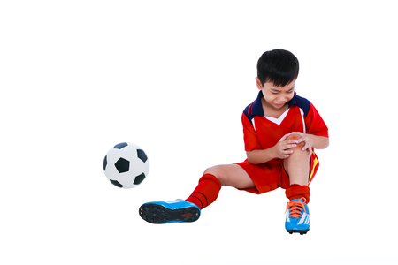 Sports injure. Youth asian soccer player with football in red uniform injured at knee. Isolated on white background. Studio shot. Full body.
