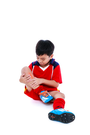 Sports injure. Youth asian soccer player in red uniform injured at shin. Isolated on white background. Studio shot. Full body.