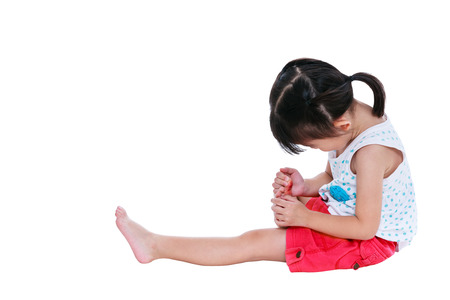 toenail: Full body of sad japanese child in pink skirt injured at toenail. Isolated on white background with copy space. Studio shot. Human healthcare and problem concept. Stock Photo