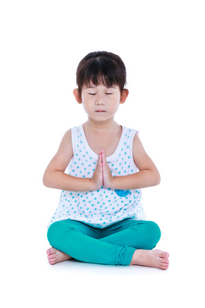 Asian pretty child with eyes closed and doing yoga exercises in lotus pose. Healthy girl practicing fitness at studio. Isolated on white background. Stock Photo