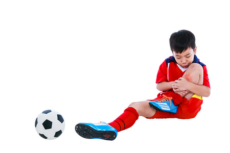 Sports injure. Youth asian soccer player with football in red uniform injured at shin. Isolated on white background. Studio shot. Full body. Stock Photo
