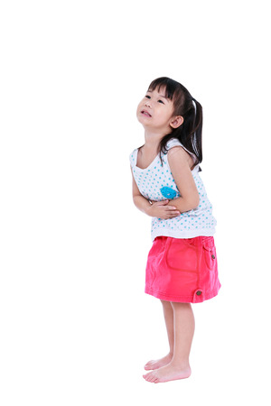 Full body of unhappy asian child in pink skirt suffering from stomachache. Isolated on white background with copy space. Studio shot. Human healthcare and problem concept.