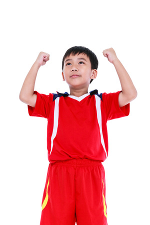 arm up: View from below of happy young asian soccer player in red uniform showing arm up gesture. Action of winner or successful people concept, studio shot. Isolated on white background.