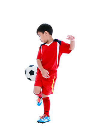 Full length portrait of happy asian soccer player in red uniform playing football, studio shot. Isolated on white background.