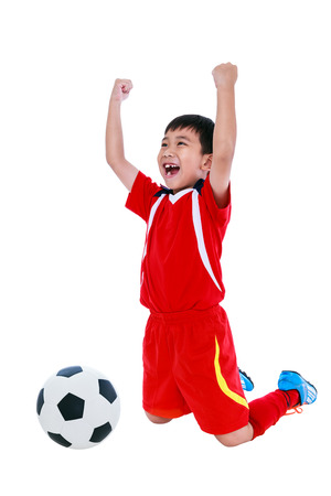 arm up: Kneeling young asian soccer player in red uniform screaming and showing arm up gesture. Action of winner or successful people concept, studio shot. Isolated on white background.