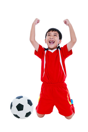 Kneeling young asian soccer player in red uniform screaming and showing arm up gesture. Action of winner or successful people concept, studio shot. Isolated on white background.