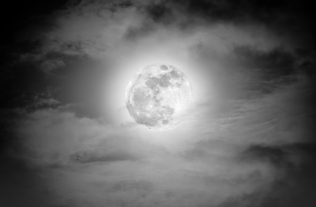nightly: Attractive photo of a nighttime sky with clouds and bright full moon. Nightly sky with beautiful full moon. Outdoors at night. Black and white tone. The moon were NOT furnished by NASA. Stock Photo