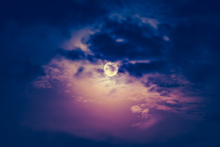 full moon effect: Attractive photo of a nighttime sky with dark cloudy and bright full moon. Full moon behind clouds at night. Vintage effect tone. The moon were NOT furnished by NASA.
