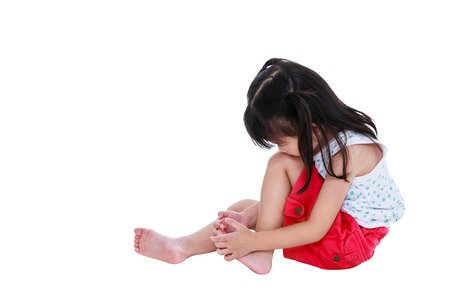 Full body of sad japanese child in pink skirt injured at toenail. Isolated on white background with copy space. Studio shot. Human healthcare and problem concept. Stock Photo