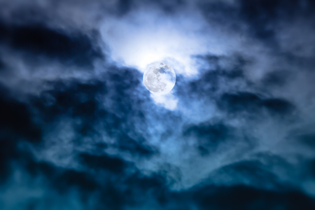 Attractive photo of background nighttime sky with clouds and bright full moon with shiny. Nightly sky with beautiful full moon behind cloud. Outdoors at night. The moon were NOT furnished by NASA.