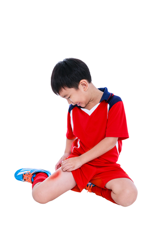 Sports injure. Youth asian soccer player in red uniform injured at thigh. Isolated on white background with copyspace. Studio shot.