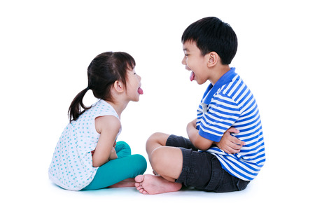 Bad behavior. full body of asian children sticking out tongues and mocking each other. Sister and brother sitting at studio, isolated on white background.