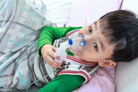 sickbed: Top view of asian child holds a mask vapor inhaler for treatment of asthma on sickbed in hospital. Breathing through a steam nebulizer. Concept of inhalation therapy apparatus. Stock Photo