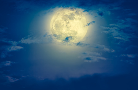 Attractive photo of a nighttime green sky with clouds and bright full moon. Nightly sky with large moon. Outdoors at night. Cross process and vintage tone effect. The moon were NOT furnished by NASA. Stock Photo