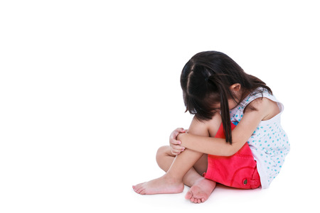 unloved: Sadness asian child barefoot sitting on floor with copy space. Isolated on white background. Negative human emotions. Conceptual about children who lack warmth and affection, abandoned children. Stock Photo